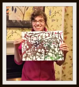 A woman with intellectual disabilities displays a painting she created.